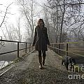 Woman Walking With Her Dog On A Bridge by Mats Silvan