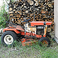 Wood Pile And Lawn Tractor by Cathy Anderson
