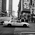 yellow cab taxi blurs past pedestrian waiting at crosswalk on Broadway outside macys new york usa by Joe Fox
