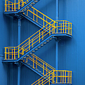Yellow Metal Staircase Against A Blue by Ozgur Donmaz