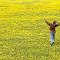 Young Boy Running Through Field Of by Gemstone Images