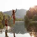 Young Couple Jumping Into River by Zave Smith