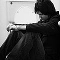 Young Dark Haired Teenage Man Sitting On The Floor Of The Bathroom With Back Against The Wall In The by Joe Fox