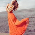 Young Woman In Orange Dress Flying In The Wind At Sea Shore by Oleksiy Maksymenko