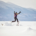 Young Woman Jumping While Snowshoeing by Chris Bennett