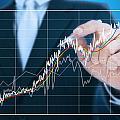Businessman Writing Graph Of Stock Market  by Setsiri Silapasuwanchai