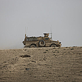 An Mrap Vehicle Patrols The Ridge by Terry Moore