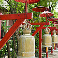 Row Of Bells In A Temple Covered By Red Umbrella by U Schade