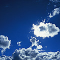 Sunlit Fluffy White Clouds In A Blue by Jason Edwards