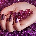Woman Hand With Purple Nail Polish On Candy by Oleksiy Maksymenko