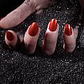 Woman Hand With Red Nails On Black Sand by Oleksiy Maksymenko
