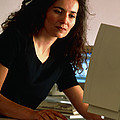 Woman Using A Personal Computer (pc) At Home by Tek Image