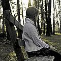 Girl Sitting On A Wooden Bench In The Forest Against The Light by Joana Kruse