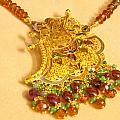 A Beautiful Intricately Carved Gold Pendant Hanging From A Semi-precious Stone Chain by Ashish Agarwal