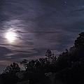 A Bright Moon Rises Through Clouds by John Davis