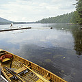 A Canoe Floats Next To A Dock by Skip Brown