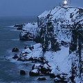 A Lighthouse Atop Snow-covered Cliffs by Tim Laman