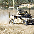 A M1114 Humvee Patrols The Perimeter by Stocktrek Images