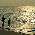 A Man And A Young Boy Fish In The Surf by Medford Taylor