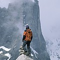 A Man Stands On A Cliff Watching by Jimmy Chin
