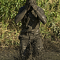 A Participant Wipes Mud From His Face by Stocktrek Images