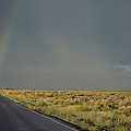 A Rainbow Touches A Rain Soaked Road by Bill Hatcher