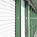 A Row Of Locked Storage Units At A Self Storage Facility by Frederick Bass