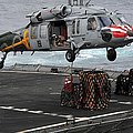 A Sailor Hooks Cargo To An Mh-60s Sea by Stocktrek Images