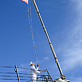 A Sailor Lowers The U.s. Navy Jack by Stocktrek Images