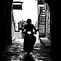 a scooter rider in the back light in a narrow street in Italy by Joana Kruse