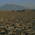 A Volcano Rises Above A Dry Lake Bed by Gordon Wiltsie