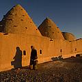 A Woman Walks Past A Sunlit Mud Brick by James L. Stanfield