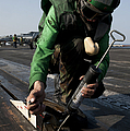 Airman Greases The Catapult Shuttle by Stocktrek Images