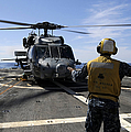 Airman Signals To An Mh-60s Sea Hawk by Stocktrek Images