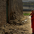 An Afghan Girl Carries Her Little by Stocktrek Images