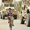 An Iraqi Boy Rides His Bike Past A U.s by Stocktrek Images