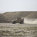 An M-atv Races Across The Wadi by Terry Moore