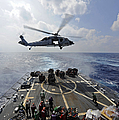 An Mh-60r Sea Hawk Transfers Supplies by Stocktrek Images