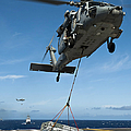 An Mh-60s Sea Hawk Helicopter Lowers by Stocktrek Images