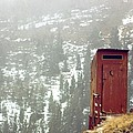 An Outhouse Perches On A Hillside by Rex A. Stucky