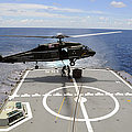 An Sh-60f Sea Hawk Helicopter Lowers by Stocktrek Images