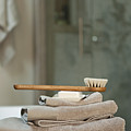 Bath Brush On Stacked Towels by Karyn R. Millet
