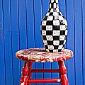 Blach And White Vase On Stool Against Blue Wall by Garry Gay