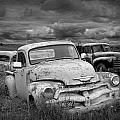 Black And White Photograph Of A Junk Yard With Vintage Auto Bodies by Randall Nyhof