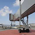 Boarding Bridge Leading To A Parked Plane by Jaak Nilson