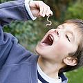 Boy Pretending To Eat An Earthworm by Ian Boddy