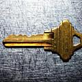Brass Key On Stainless Steel. by Ballyscanlon