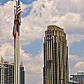 Buildings And Flags Against Sky by Susan Leggett