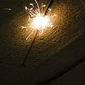 Burning Sparkler On Sidewalk At Night by Roberto Westbrook