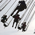 Carnival Goers Enjoy A Ride At An by Stacy Gold